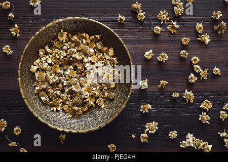 Brass Bowl of Dried Chamomile Flowers on Dark Table - Stock Image