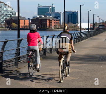 Cyclists ( vintage style) riding along Trafford Wharf , Salford Quays, Salford / Manchester, UK - Stock Image
