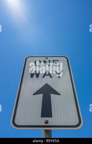 One Way sign pointing toward a blue sky, with sun flare. - Stock Image