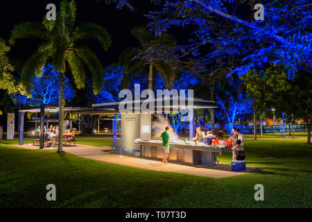 People cooking a barbecue at night in an illuminated park, Cairns Esplanade, Far North Queensland, FNQ, QLD, Australia - Stock Image