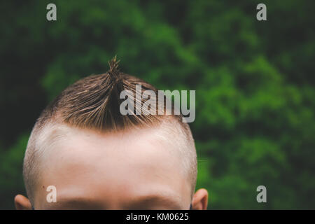 The top of a boy's head with a fauxhawk haircut. - Stock Image