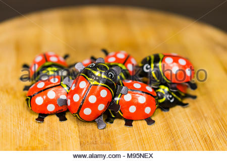 Poznan, Poland - March 18, 2018: Ladybird shaped packed chocolate on a wooden board in soft focus - Stock Image