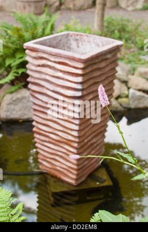 A sculpture graces the lush water garden at Koi Gardens, Spokane, Washington State, USA. - Stock Image