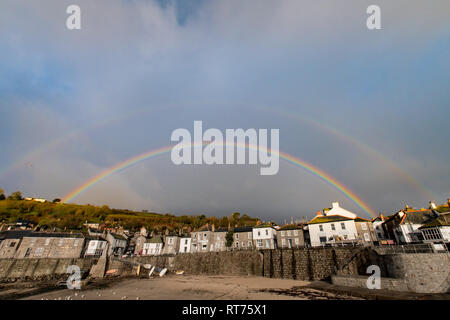 Mousehole, Cornwall, UK. 28th Feb 2019. UK Weather. Sharp showers over Mousehole this morning, bringing with them a beautiful double rainbow over the village. Credit: Simon Maycock/Alamy Live News - Stock Image