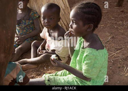 Samba village, Yako Province, Burkina Faso : Children eating fruit. - Stock Image