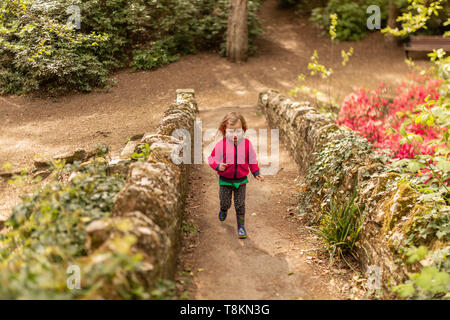 Colour portrait photograph of young girl exploring Branksome chine gardens at speed. Poole, Dorset, England. - Stock Image