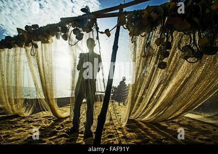 Fisherman mending nets on the Turtle Islands, Sierra Leone. - Stock Image