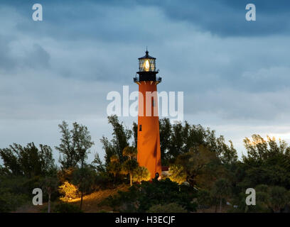 The orange brick tower of Jupiter Lighthouse , Florida, still shines out to sea as dawn comes up on a cloudy morning. - Stock Image