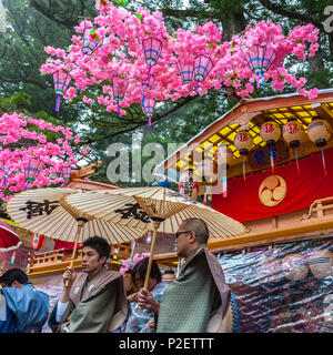 Two men with umbrellas in front of decorated festival wagon during Yayoi Matsuri in Nikko, Tochigi Prefecture, Japan - Stock Image