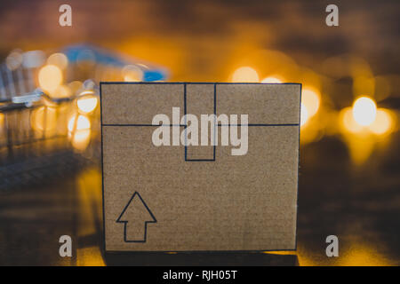 cardboard delivery parcel box on wooden desk with shopping basket and fairy lights in the background, concept of online purchases and shipping - Stock Image
