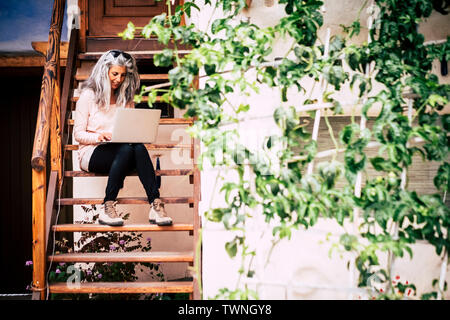 Adult alternative diversity people concept white and grey long hair beautiful woman with laptop computer sitting on a wooden stairs outside home - hap - Stock Image
