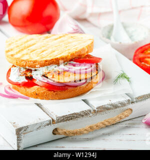 Sandwich with fried chicken breast, tomatoes, red onions and tzatziki sauce. Gourmet appetizer. Selective focus, square picture - Stock Image
