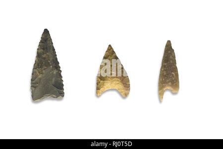 Three serrated stone arrowheads. Isolated over white background - Stock Image