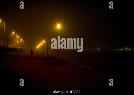 Person walking along deserted waterfront at night - Stock Image