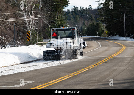 A Prinoth  Husky snow groomer driving down the side of the highway to cross a bridge in Speculator, NY USA part of a snowmobile trail. - Stock Image
