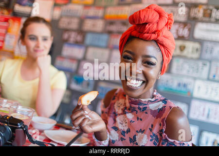 Portrait enthusiastic young woman in restaurant - Stock Image