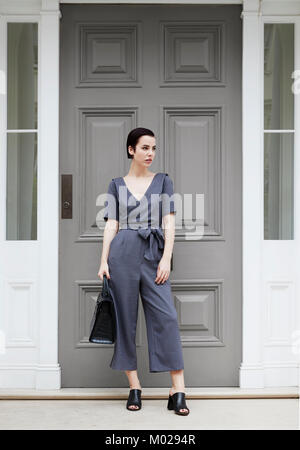 Chic woman in jumpsuit standing outside smart London house - Stock Image