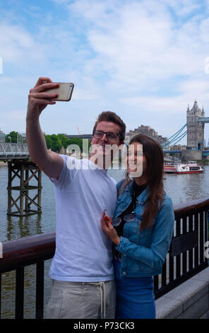 London, England. 4th July 2018. A couple on holiday from their home in Belgium take a selfie near London's Tower Bridge on another very hot day. The present heatwave is set to continue. ©Tim Ring/Alamy Live News - Stock Image