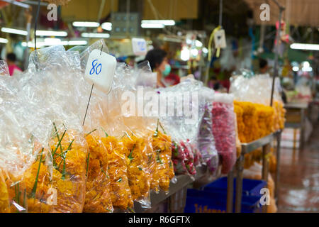 Famous Bangkok flower market. This is one of the many corridors in the covered market, lined with stalls selling wholesale petals used for decorative  - Stock Image