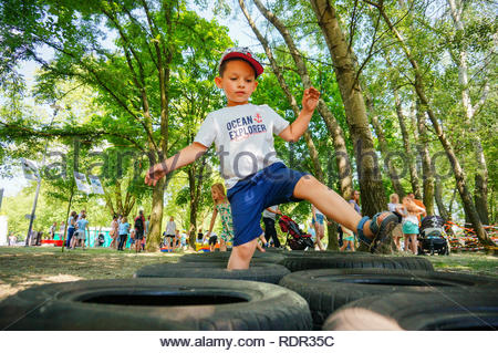 Poznan, Poland - May 27, 2018: Young boy walking on obstacle made of tires on the Kindernalia event at the Jan Pawla II park - Stock Image