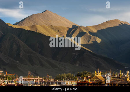 Golden pinnacles of Jokhang temple among a lots of roofs of houses in Lhasa city and late afternoon sunlight on - Stock Image