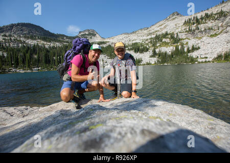 Portrait of a father and son on the shore of Beehive Lake while on a hiking trip, Selkirk Mountains, Sandpoint, Idaho, USA - Stock Image