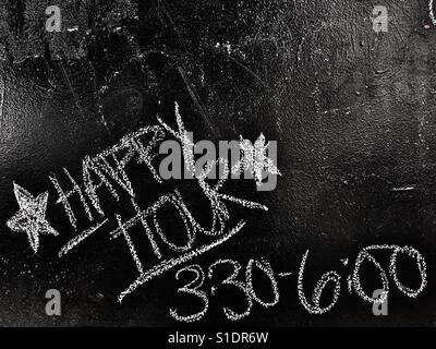Happy hour on bar chalk board - Stock Image