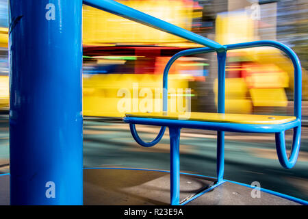 the carousel seat rotates with a blurred background - Stock Image
