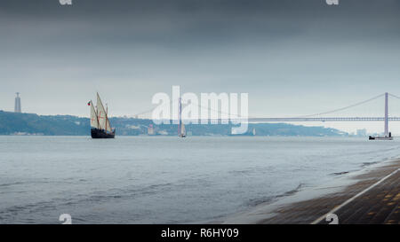 Traditional Portuguese caraval on River Tagus, Lisbon, Portugal with 25 April Bridge in background. - Stock Image