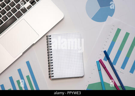 Modern workspace with blank notepad, laptop, pens on desktop. Top view. - Stock Image