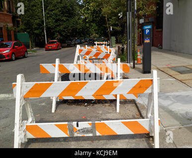 Construction safety wood carriers in white an orange on a Brooklyn street. - Stock Image