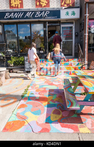 Colourful painted entrance of walkway, stairs and picnic table in front of Banh Mi Bar in Kensington Market in downtown - Stock Image