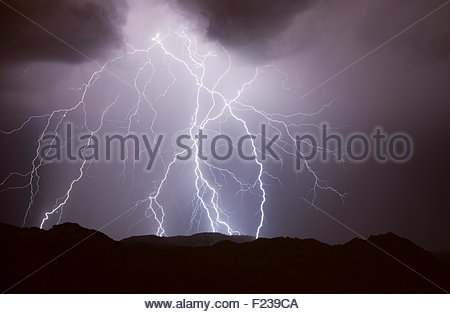 Lightning strikes top of the Catalina Mountains at night in a summer monsoon thunderstorm, north of Tucson Arizona. - Stock Image