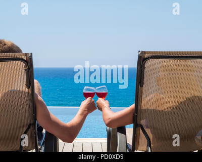 Lovers clinking glasses on holiday by an infinity pool overlooking the sea - Stock Image