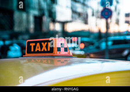Close-up taxi sign on top of a yellow cab roof in big city - Stock Image