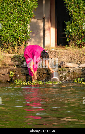 Vertical portrait of a lady doing the washing up on the riverbank in Alleppy, India - Stock Image