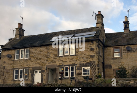Solar water heating panels on a traditional stone cottage in the famous plague village Eyam - Stock Image