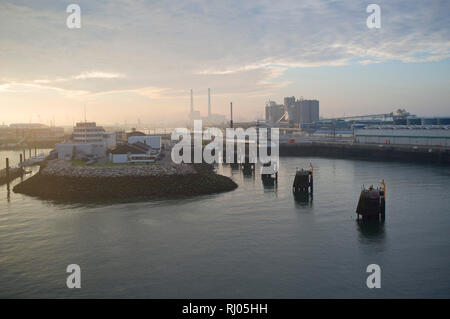 Arriving in the Port of Le Havre, France, at dawn with the iconic chimneys of the power station in the distance. - Stock Image