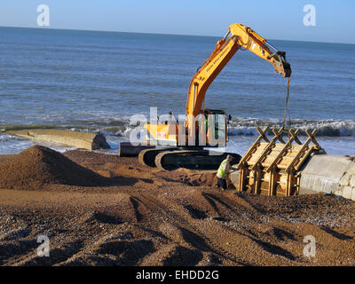 A Caterpillar Digger and Thorne Civil Engineering workers prepare to remove wooden moulding from new concrete Groynes - Stock Image