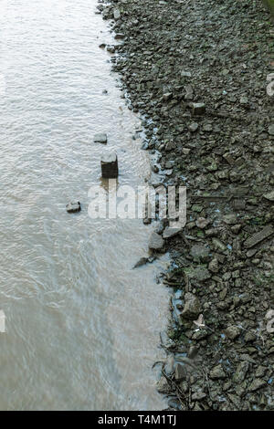 The River Thames at low tide exposing a rubble strewn riverbank in london. - Stock Image