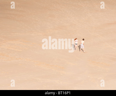 A young couple on a sandy beach in Tynemouth, UK - Stock Image