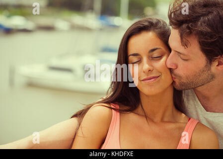 Boyfriend kissing girlfriend on cheek - Stock Image