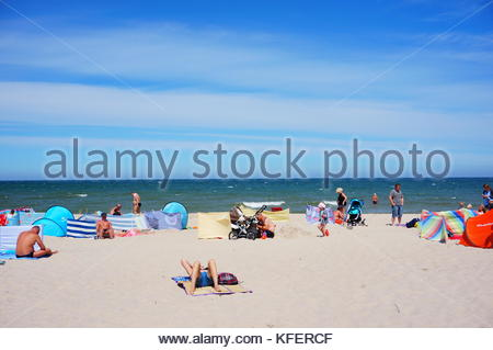 People with tents and wind protection resting on a beach in Sianozety, Poland - Stock Image