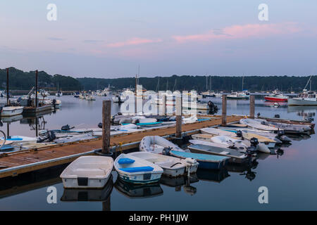 Dinghies tied up at Lake Street Landing and boats moored on Lake Tashmoo shortly after sunrise in Tisbury, Massachusetts on Martha's Vineyard. - Stock Image