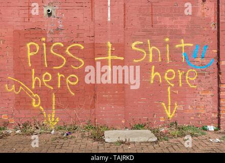 Rude graffiti on wall - Stock Image