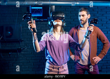 Young woman trying virtual reality with headset standing with man assistant in the playing club - Stock Image