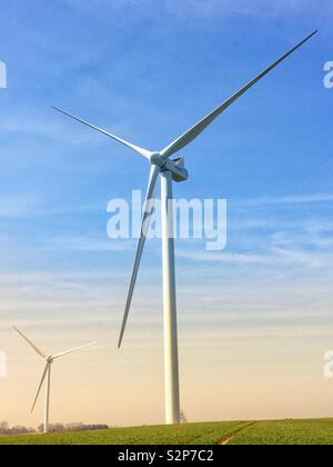 A tall wind power wind mill turbine generating clean electricity in a power or energy generation image with blue sky - Stock Image