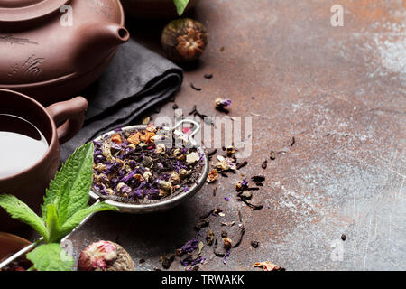 Herbal and fruit dry teas on stone table. With copy space - Stock Image