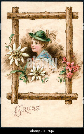 A postcard printed in Germany, shows a girl in a Tyrolean hat in a wooden frame with flowers. The inscription in - Stock Image