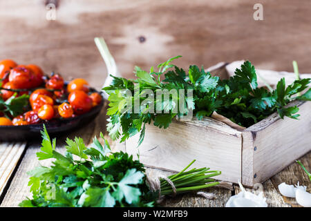 Crate of freshly picked organic  parsley, roasted cherry  tomatoes, and fresh garlic on rustic wooden table, plant based food, close up, selective foc - Stock Image